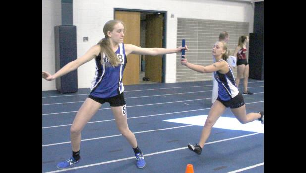 Kelsey Stortz, right, hands the baton to Mikayla Lane during the 4x800 during a recent meet.